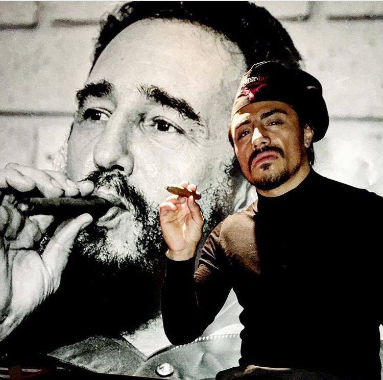 Saltbae poses with a cigar in front of a photo of Fidel Castro smoking a cigar
