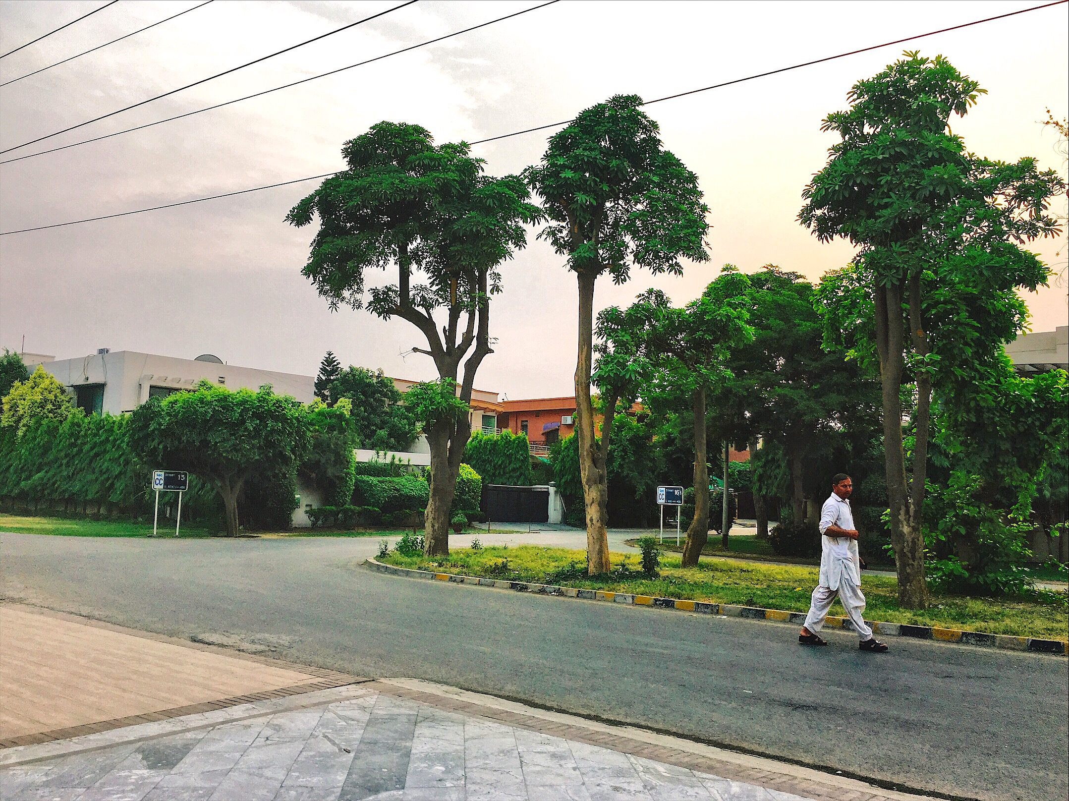 A man walks across the street in the scenic neighborhood of Defence, in Lahore, Pakistan