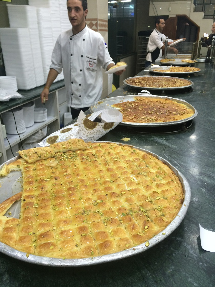 A man serves traditional knafeh pastry at a sweets shop in Amman, Jordan