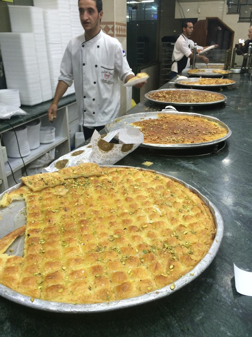 A man serves traditional knafeh pastry at a sweets shop in Amman, Jordan