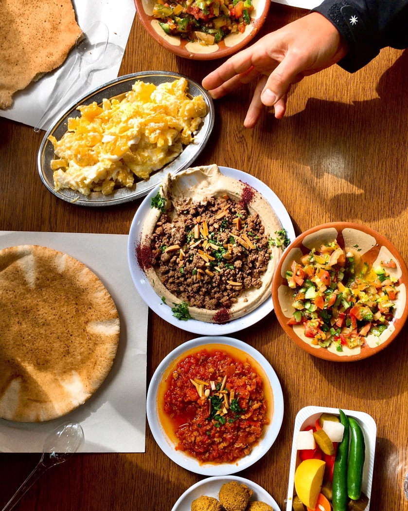 Hummus with meat and pine nuts, baked eggs with potato, falafel, fattoush, tea with fresh mint andkhubzbread